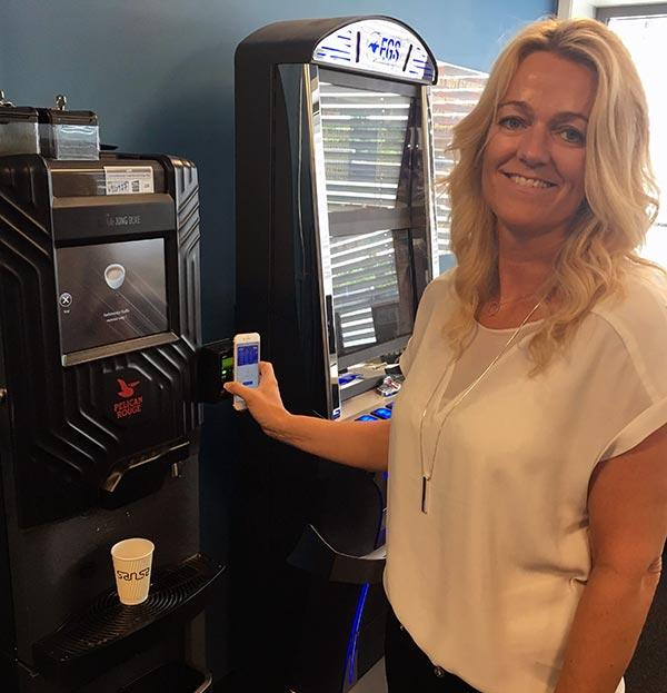 Betale med mobil på kaffeautomat. Foto.