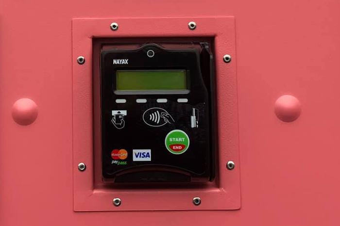 Svart Nayax betalingsterminal montert på rosa toalettvegg i Forsand